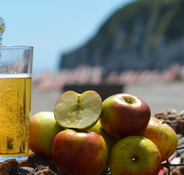 Jack Ratt cider being poured next to apples