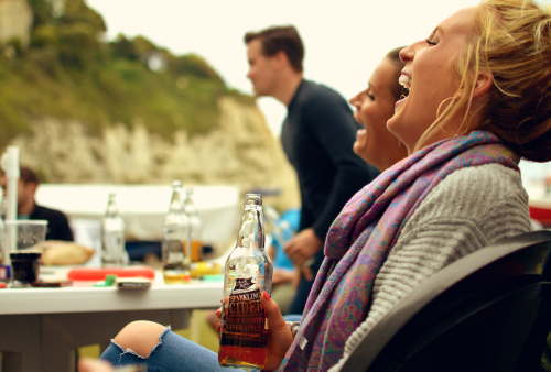 A woman laughing at a cider festival while drinking Jack Ratt cider
